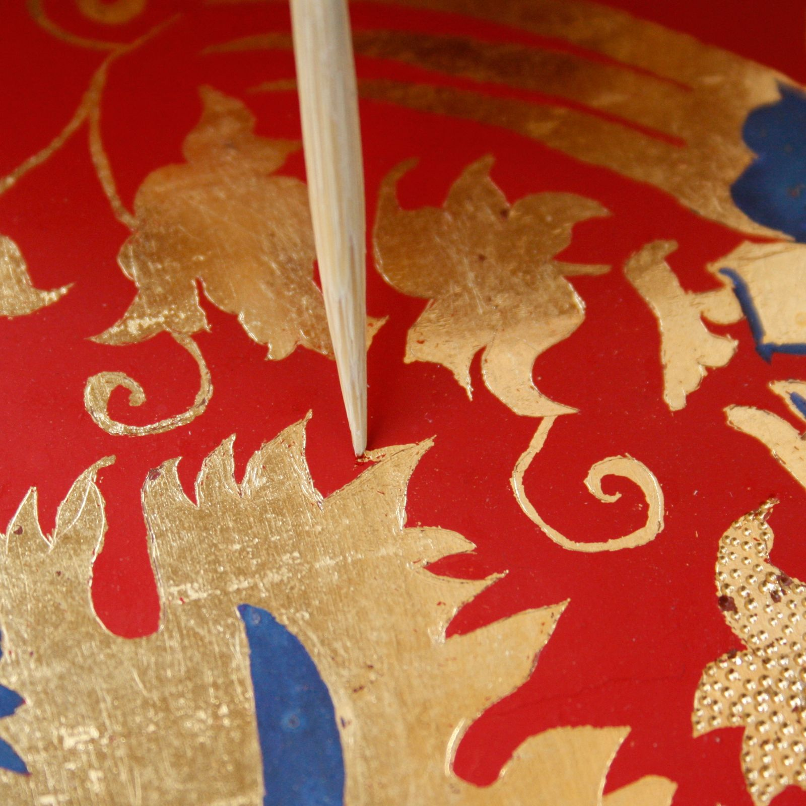 The patterns are made using sgraffito. Red paint is scraped away using a bamboo stick, revealing the gold underneath