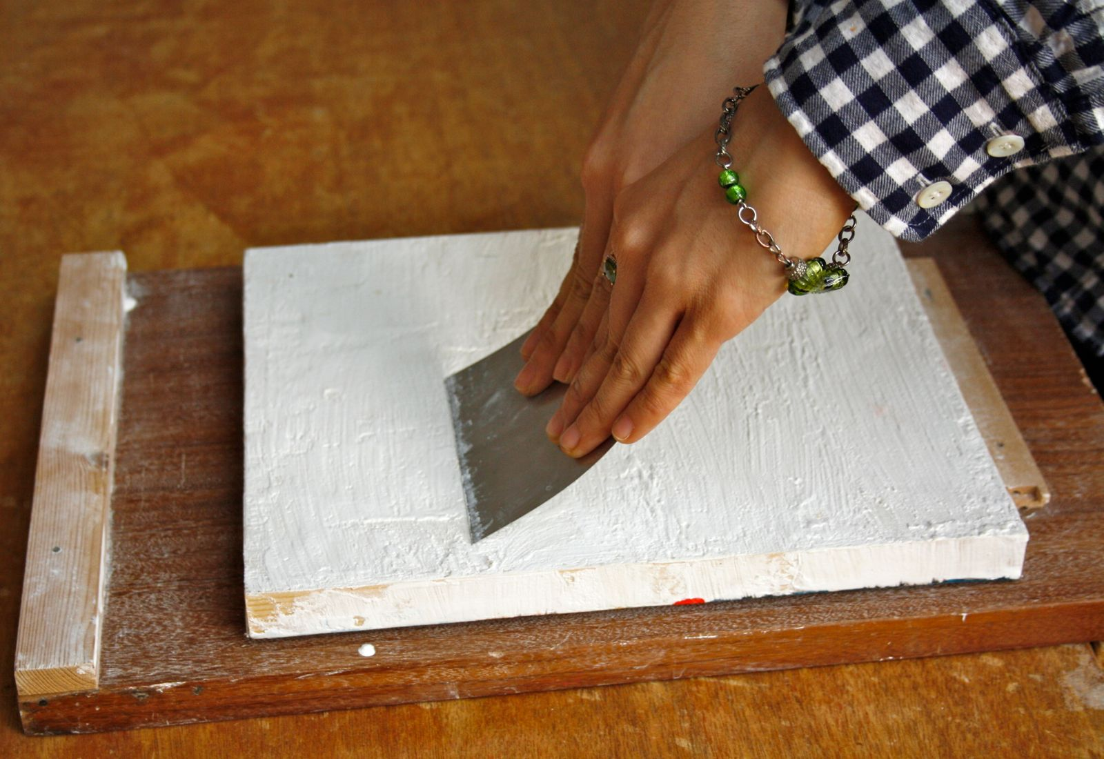 Scraping the gesso smooth using a metal scraper